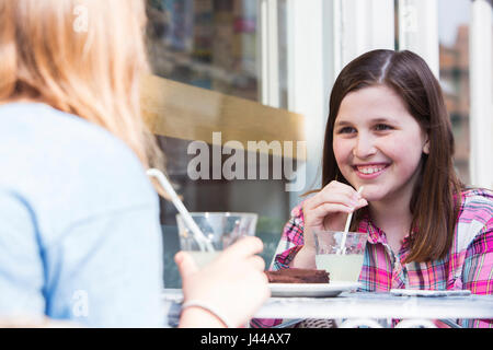 Two Young Girls Chatting At Outdoor Cafe Table - Stock Photo