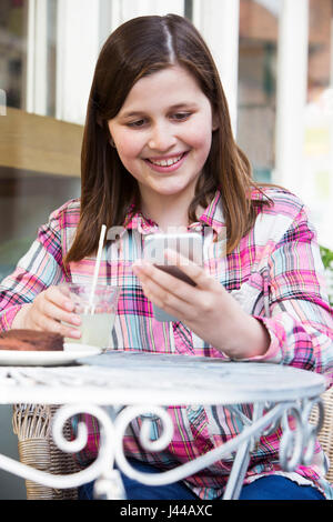 Young Girl At Cafe Reading Text Message On Mobile Phone - Stock Photo