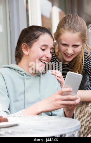 Two Young Girls At Cafe Reading Text Message On Mobile Phone