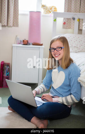 Portrait Of Girl Sitting On Floor Of Bedroom Using Laptop - Stock Photo