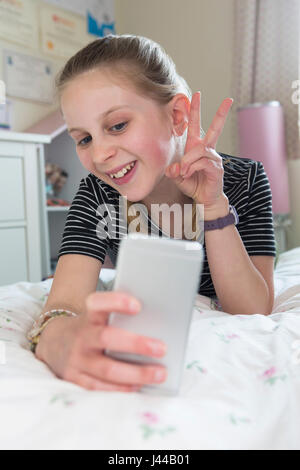 Young Girl Posing For Selfie In Bedroom - Stock Photo