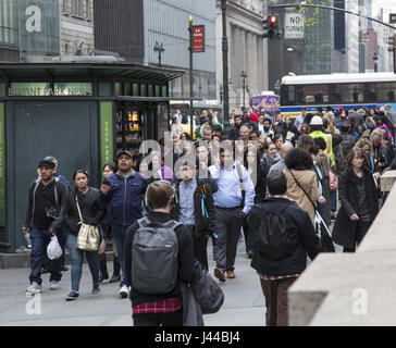 The sidewalk is always crowded on 42nd Street along the New York Public Library between 5th and 6th Avenues in NYC. - Stock Photo