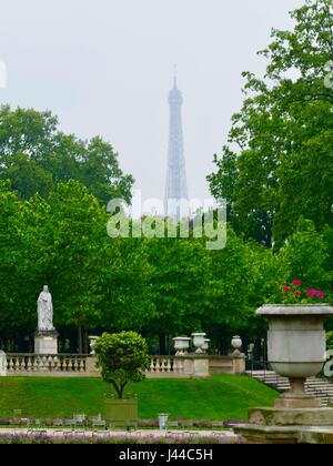 Eiffel Tower seen in almost silhouette through the clouds. Rainy day in the Luxembourg Gardens. Paris, France - Stock Photo