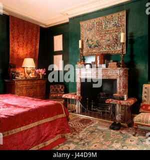 19th century Zeigler carpet with 17th century Brussels wall tapestry hanging over French Languedoc marble fireplace - Stock Photo