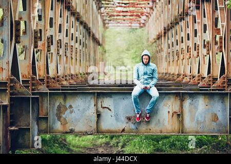 Sad man with mobile phone on the abandoned rusty bridge. Concept for sadness, loneliness, connection and more. - Stock Photo