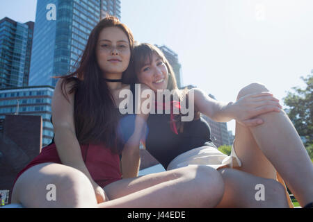 Two young women sitting down - Stock Photo