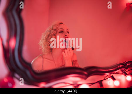 A young woman applying lipstick in a mirror. - Stock Photo