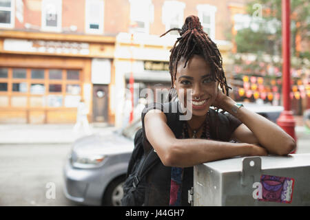 A young woman leaning against a metal box. - Stock Photo