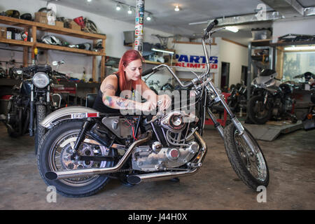 A young woman repariing a motorcycle. - Stock Photo