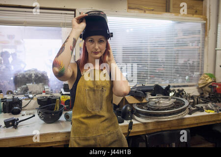 A young woman in a dirty apron and welding mask. - Stock Photo