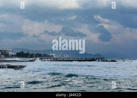 Seascape with powerful waves hitting coast of Mediterranean town during storm and mountains blurred in background - Stock Photo