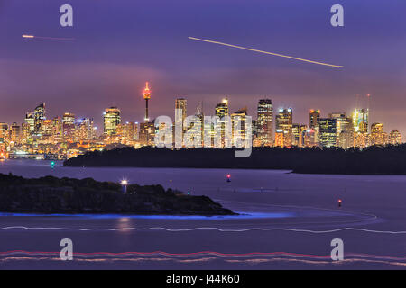 Cityline of Sydney CBD over harbour blurred waters and sandstone shore heads at sunset when the city is brightly illuminated.