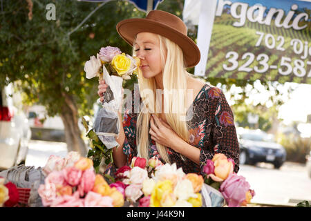 Young woman smelling fresh flowers at the farmers market - Stock Photo