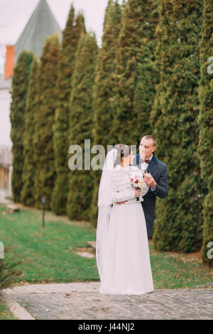 Handsome groom tenderly holding hand of his elegant new wife while both posing near cypress row in green park - Stock Photo