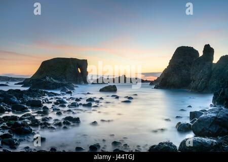 Sunset at Elephant Rock at Carricknaford a coastal scene of rocky shore near Ballintoy and Whitepark Bay on the - Stock Photo