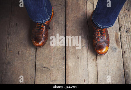 Man in interesting brown shows on wooden floor. - Stock Photo