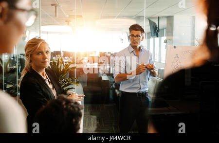 Mature businessman making a presentation on a flip-chart and discussing. Business team during strategy meeting in - Stock Photo