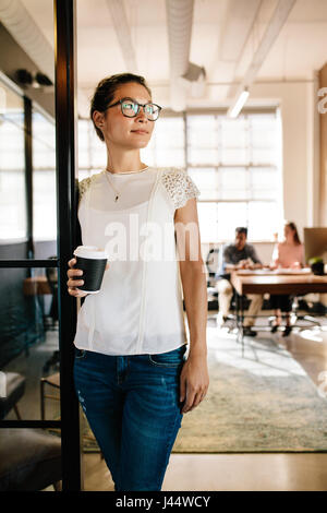 Portrait of beautiful young woman standing in office doorway with coffee. Female executive having coffee break with colleagues working in background.