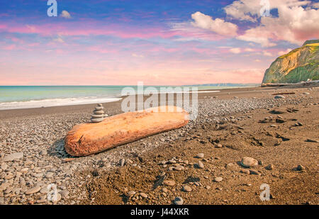 A pile of stones on a large piece of driftwood washed up on a beach in New Zealand. - Stock Photo