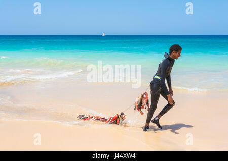 CAPE VERDE SAL young boy in wetsuit on Ponta Preta beach near  draging a catch of fishing on a line behind, santa - Stock Photo