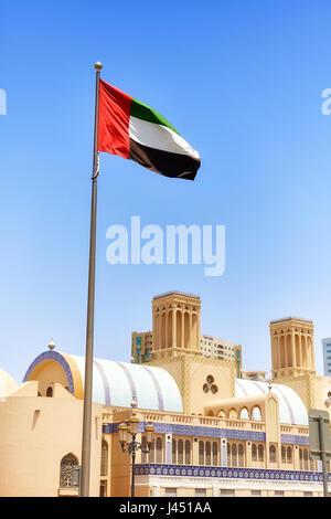 United Arab Emirates flag against blue sky in Sharjah, selective focus, United Arab Emirates. - Stock Photo