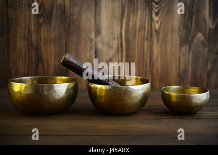 Tibetan handcrafted singing bowls with sticks on wooden background - Stock Photo