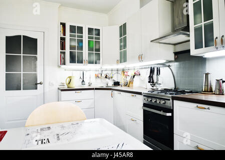 Interior of the kitchen in Scandinavian style with white furniture and a dining table - Stock Photo