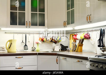 A fragment of the Scandinavian style kitchen with rail system and kitchen utensils - Stock Photo