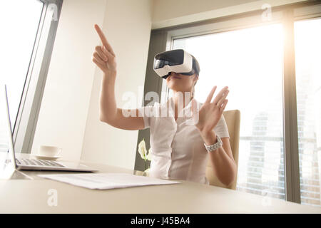 Business woman wearing virtual reality glasses - Stock Photo