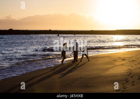 Silhouettes of a family on a beach at sundown (Tenerife, Spain) - Stock Photo
