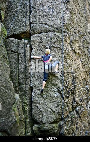 Young female climber climbing a route on a rock. Sokoliki, Poland - Stock Photo