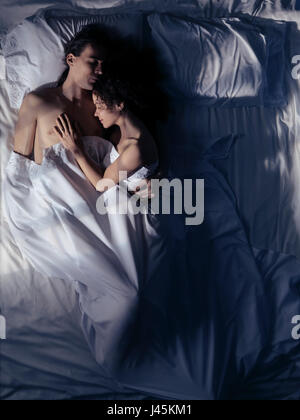 Couple sleeping together in an enbrace at night in bed in a dark simly lit by moonlight bedroom - Stock Photo