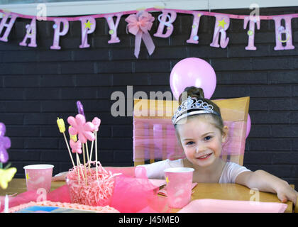 Smiling happily, little girl poses at her birthday party.  She is sitting at the table with cup and decorations. - Stock Photo