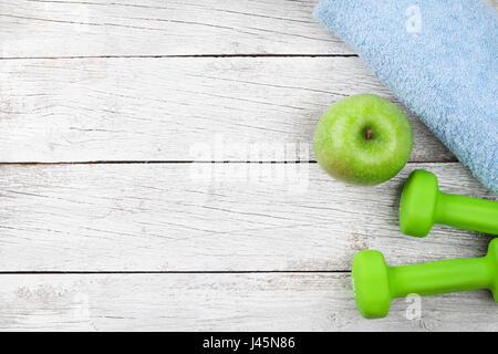 Fitness concept. Dumbbells and apple on wooden background. Top view with space for your text - Stock Photo