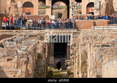 An interior view of the amphitheatre inside the Colosseum with tourists visitors on a sunny day taken from ground - Stock Photo
