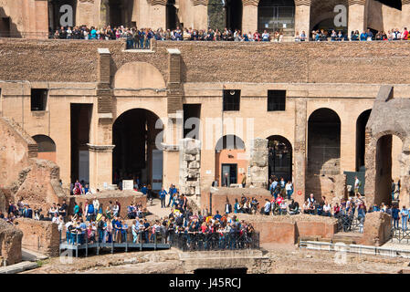 A compressed perspective interior view of the amphitheatre inside the Colosseum with tourists visitors on a sunny - Stock Photo