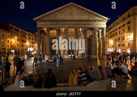An exterior view of tourists visitors outside the Pantheon in Rome at night, evening, dusk.