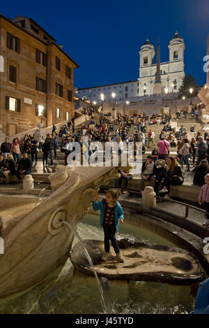 Spanish Steps in Rome a tourist posing for a photograph on the Fountain of the ugly Boat evening, night with the - Stock Photo