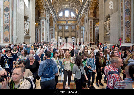 A wide angle interior view inside St Peter's Basilica of the main alter and crowds of tourists and visitors. - Stock Photo