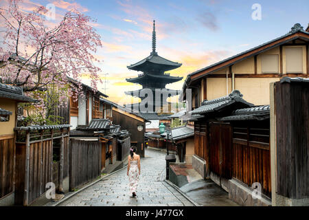 Asian woman walking Yasaka in street near Pagoda in the Morning, Kyoto, Japan - Stock Photo