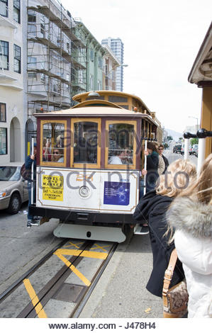 People standing on sideboards and holding onto grab bars of cable car as they pass another cable car, San Francisco, - Stock Photo