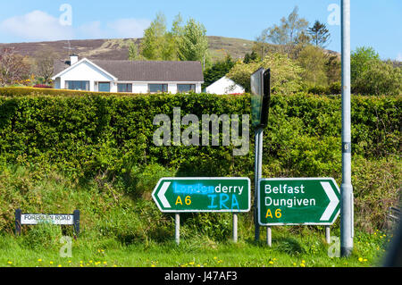 Defaced road sign near Claudy in County Londonderry, Northern Ireland UK. - Stock Photo