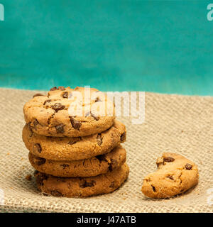 A square photo of chocolate chips cookies, shot on a burlap and teal blue background textures - Stock Photo