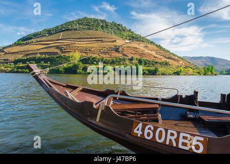Portugal Douro Valley, prow of a traditional rabelo boat moored on the Douro River with a large terraced vineyard - Stock Photo