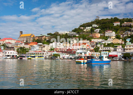 Boats in the Carenage surrounded by colourful buildings on a hill in St. George's, capital of Grenada, West Indies, - Stock Photo