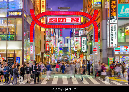 TOKYO, JAPAN - MAY 7, 2017: Crowds pass through Kabukicho in the Shinjuku district. The area is an entertainment - Stock Photo
