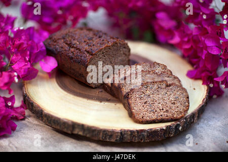 Homemade Banana Walnut bread sliced and displayed on wood-grain cutting board surrounded by pink bougainvillea flowers - Stock Photo