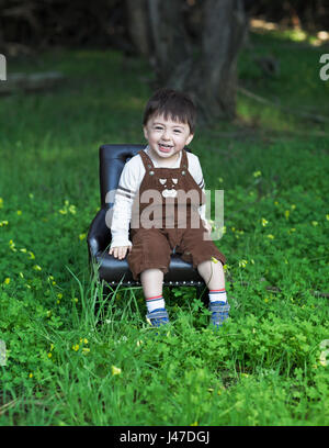 Cute laughing little boy wearing brown corduroy overalls sitting in a blue leather chair in a green meadow - Stock Photo