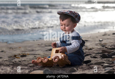 Cute toddler little boy wearing blue denim overalls and a newsboy cap sitting in the sand at the beach near the - Stock Photo