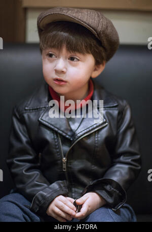 Little mixed race Asian Caucasian boy with brown hair wearing a black leather rockabilly motorcycle jacket with - Stock Photo